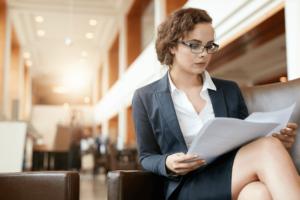 portrait-of-businesswoman-reading-document-female-professional-in-hotel-lobby-examinin-SBI-301326769